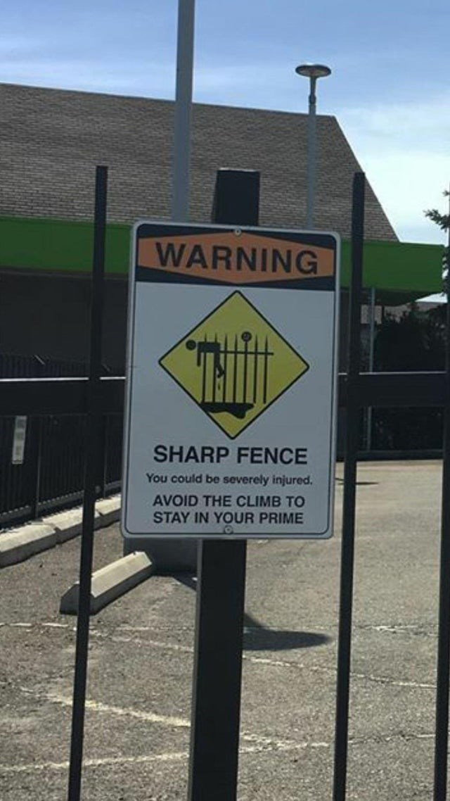Sign - WARNING SHARP FENCE You could be severely injured AVOID THE CLIMB TO STAY IN YOUR PRIME