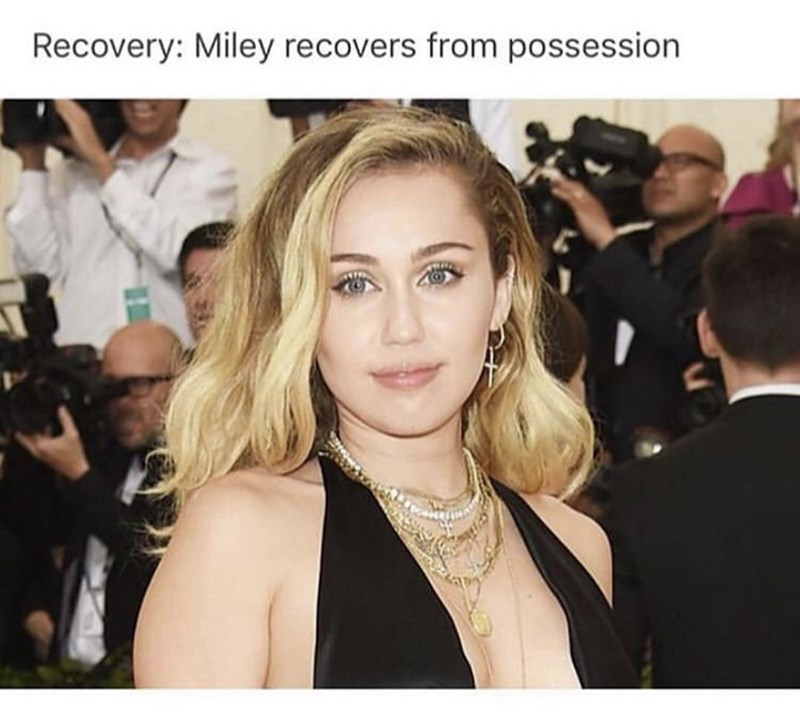 miley cyrus with medium length blonde hair smiling innocently at camera