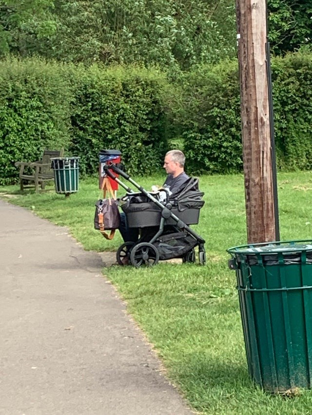 illusion that looks like a man is the baby in the carriage in a park
