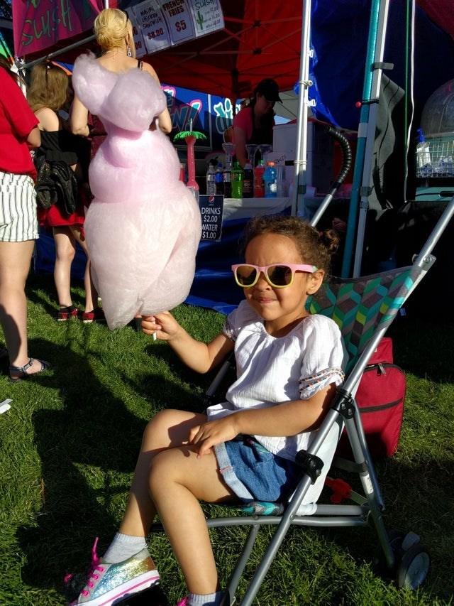 little girl wearing sunglasses in pram holding fairy floss looks like a woman is wearing the fairy floss