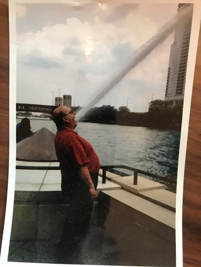 man opening his mouth with fountain behind him looks like he is spraying water from his mouth