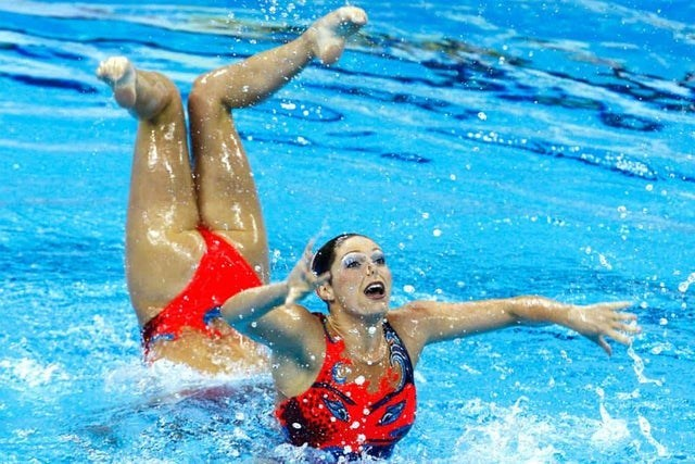 two women swimming in pool wearing red swimmers look like one long person