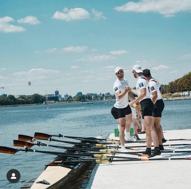 men standing next to rowing boat in water