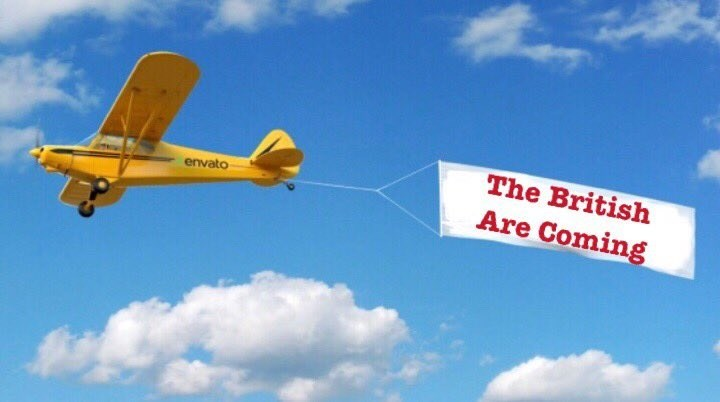 a yellow plane flying against a blue sky pulling a sign behind it with red writing
