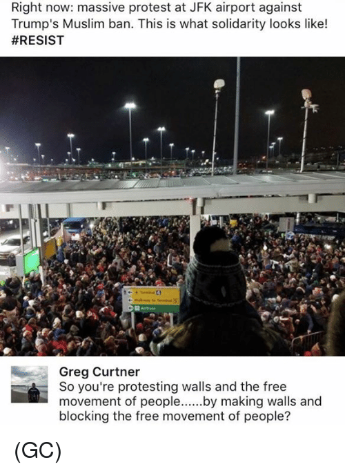 a crowd of people stand outside JFK airport at night