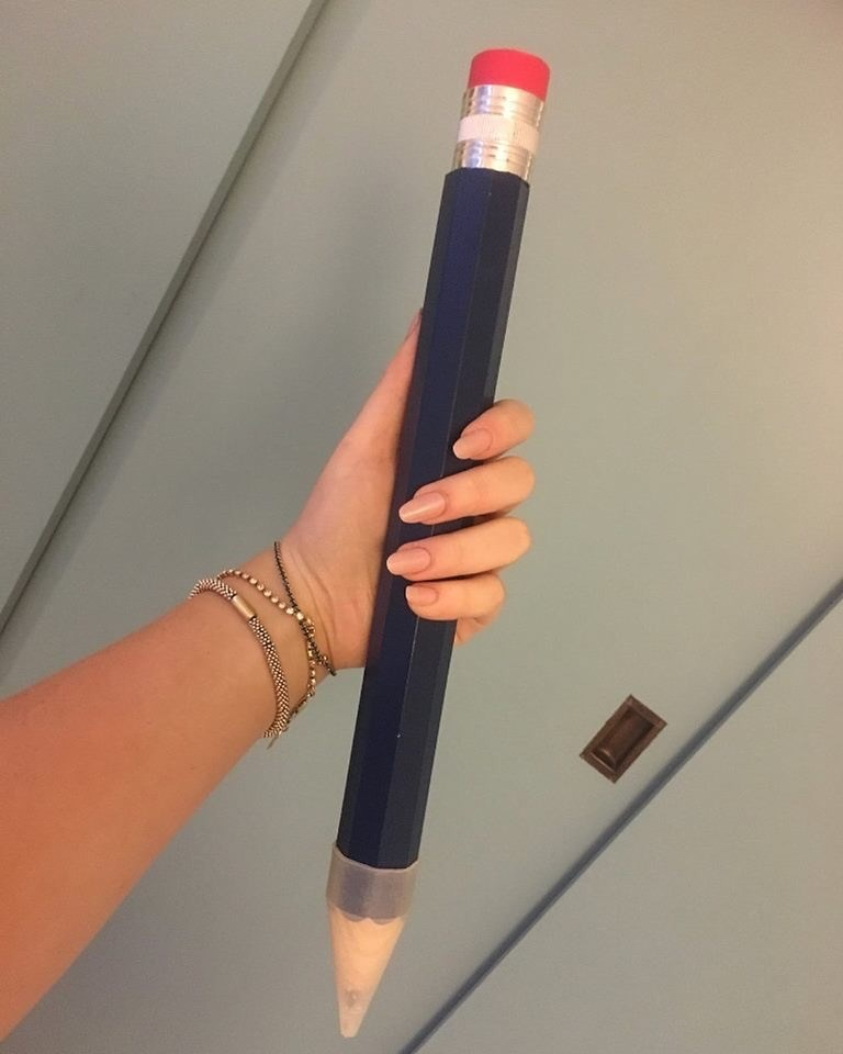 Funny picture of a woman holding a very large pencil
