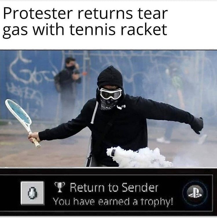 Photo caption - Protester returns tear gas with tennis racket 3A TReturn to Sender You have earned a trophy! B