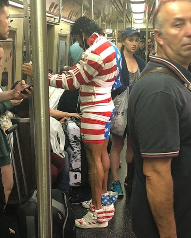 Funny picture of a guy on the subway dressed in an American flag costume