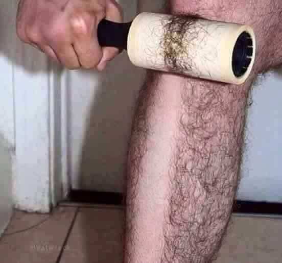 Photo of a man 'shaving' his legs using a lint roller