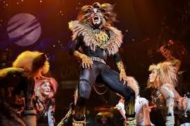 photo of cats actors dancing on stage in cat costumes
