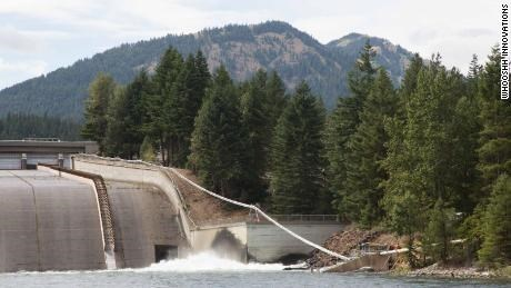 salmon cannon seen from far away going over a dam wall