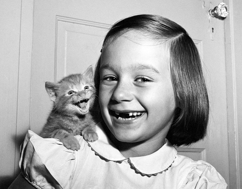 black and white photo of little girl with kitten on her shoulder both are smiling