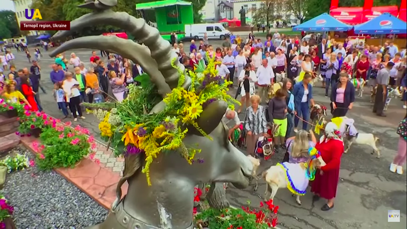 goat statue with flowers on head in front of crowd