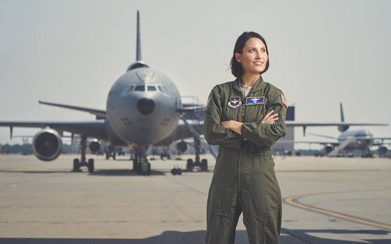 picture woman in air force green jumpsuit standing with crossed arms in front of air force plane