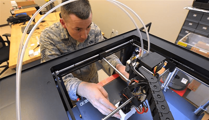picture of air force employee fixing a 3d printer