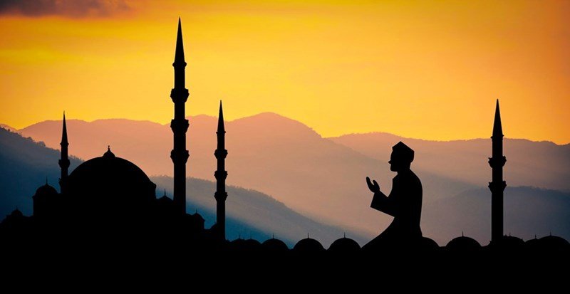 silhouette of man praying in front of mosque towers with sun setting over mountains