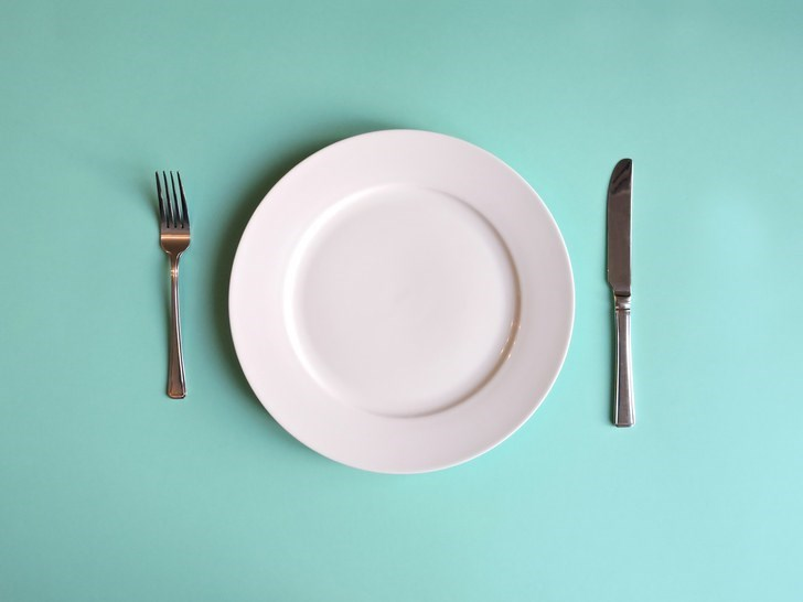 picture of white plate with knife and fork on blue table