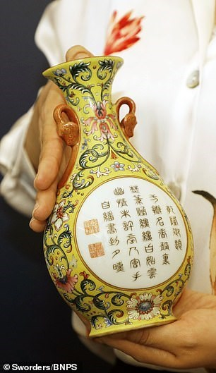 someone's hands holding a small yellow vase with chinese writing on it
