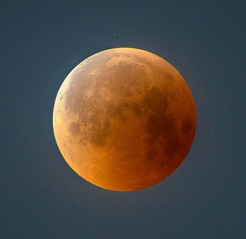 picture of orange moon against blue sky lunar eclipse