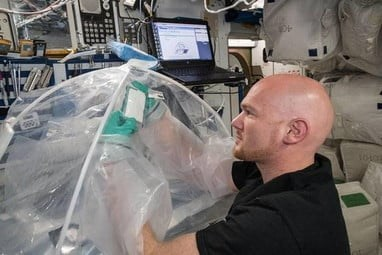 male astronomer mixing cement in bag in space