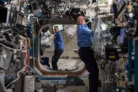 picture two astronauts on ISS mixing cement in bags