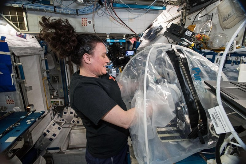 picture female astronaut in ISS mixing cement in bag