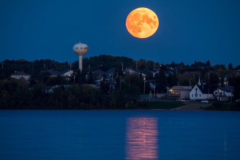 yellow orange harvest moon rising over city and river