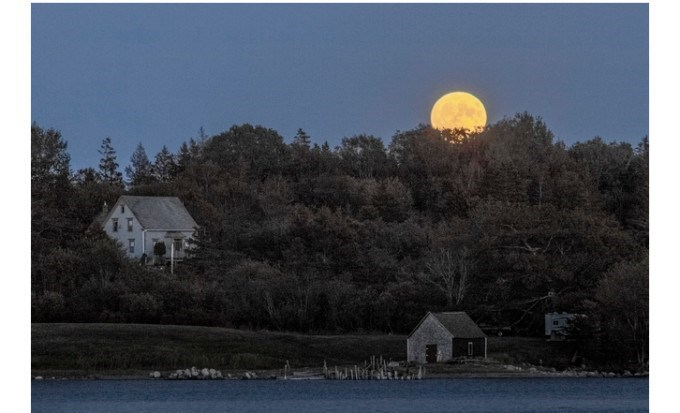 yellow harvest moon rising behind mountain with small huts