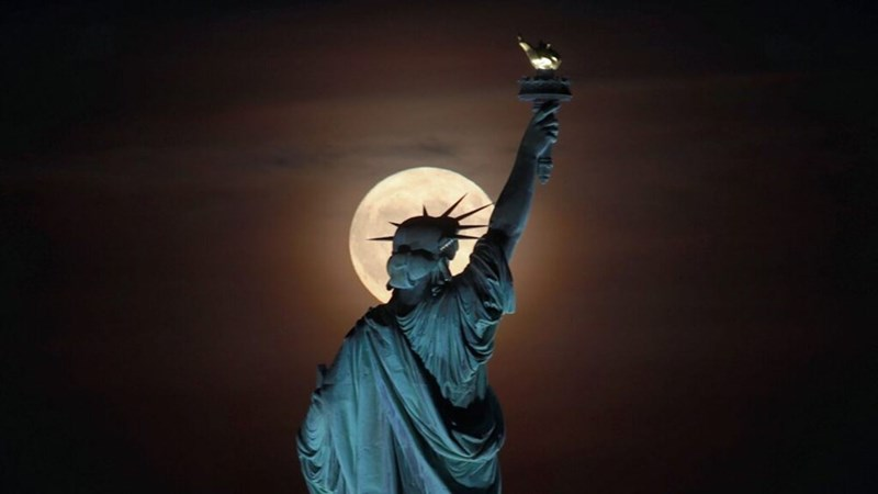 harvest moon rising behind statue of liberty