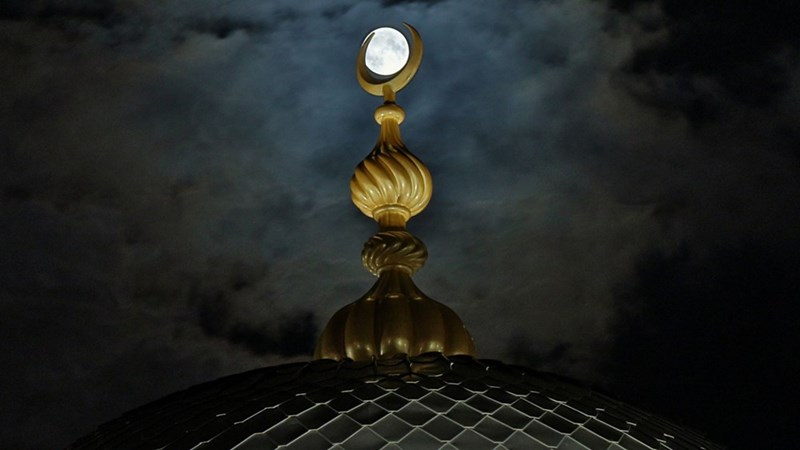 harvest moon inside the crescent moon shape on top of mosque in turkey