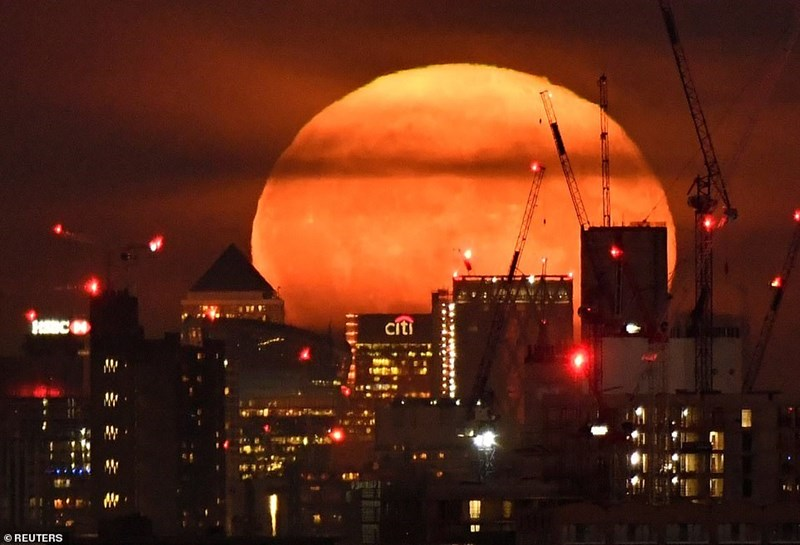 red harvest moon behind buildings and cranes