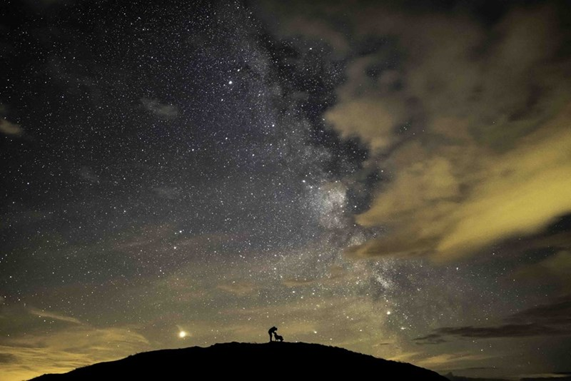 silhouette man and dog against milky way in sky
