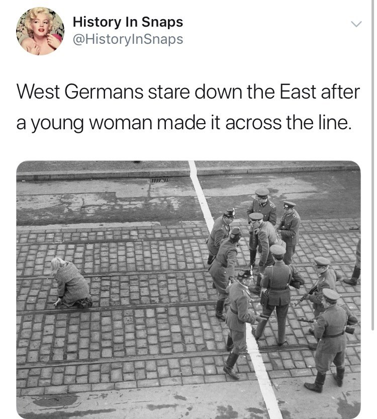 Text - History In Snaps @HistoryInSnaps West Germans stare down the East after a young woman made it across the line.