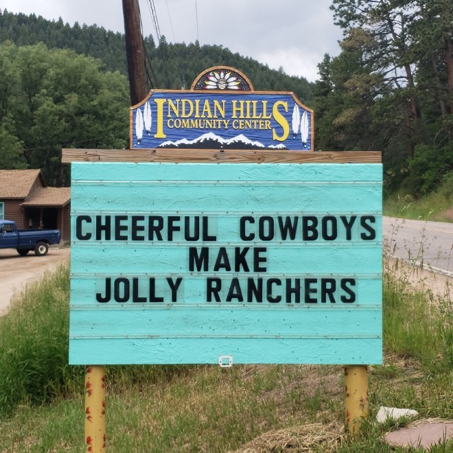 Street sign - SM TNDIAN HILL COMMUNITY CENTER CHEERFUL COWBOYS MAKE JOLLY RANCHERS