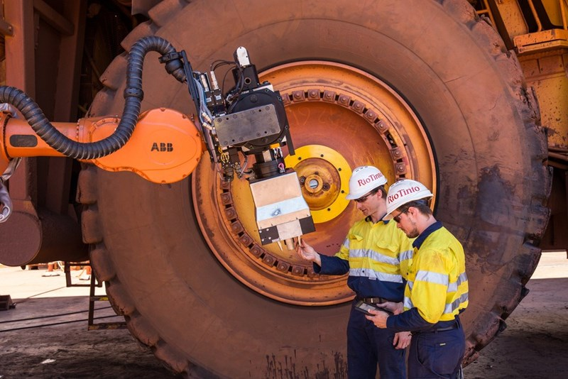 two men standing next to large wheel of autonomous mining truck