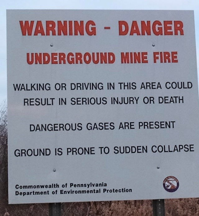 Text - WARNING DANGER UNDERGROUND MINE FIRE WALKING OR DRIVING IN THIS AREA COULD RESULT IN SERIOUS INJURY OR DEATH DANGEROUS GASES ARE PRESENT GROUND IS PRONE TO SUDDEN COLLAPSE Commonwealth of Pennsylvania Department of Environmental Protection