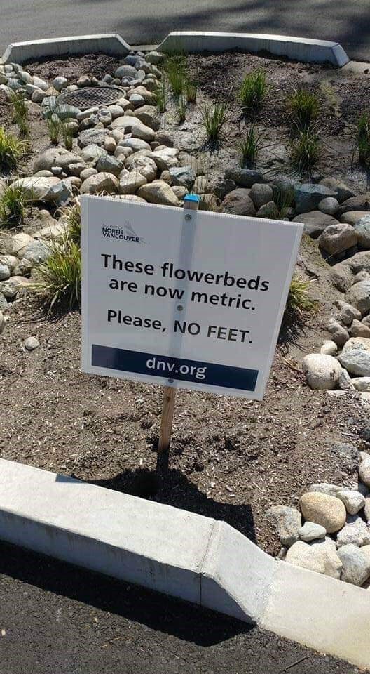 Sign - NORTH VANCOUVER These flowerbeds are now metric. Please, NO FEET. dnv.org