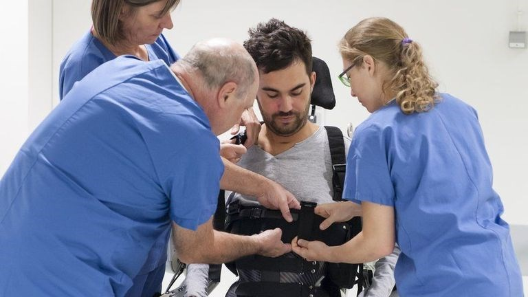 scientists strapping paralyzed man into exoskeleton to walk