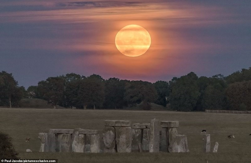 huge hunter's moon behind clouds hanging over stonehenge