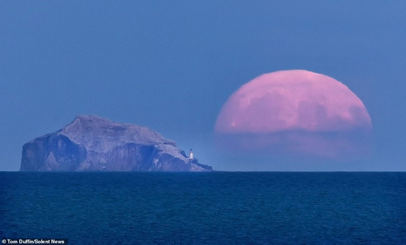 gigantic hunter's moon next to rock in the ocean with tiny lighthouse