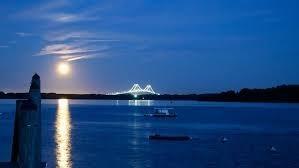 hunter's moon reflecting on water near illuminated bridge
