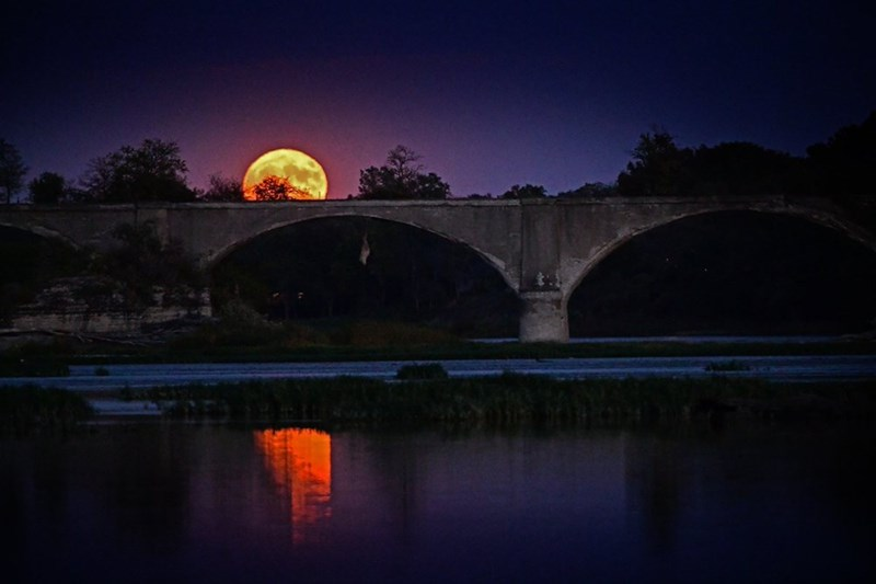 hunter's moon rising over romantic arched bridge in france