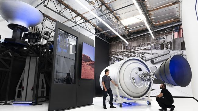 picture two men standing next to big rocket pieces 3d printed relativity space