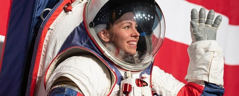 woman in new spacesuit by nasa smiling waving in front of american flag