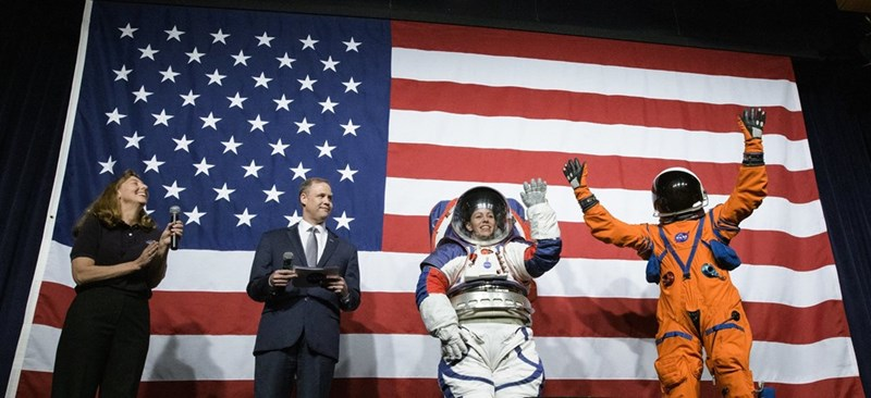 picture two people in new astronaut space suits in front of american flag