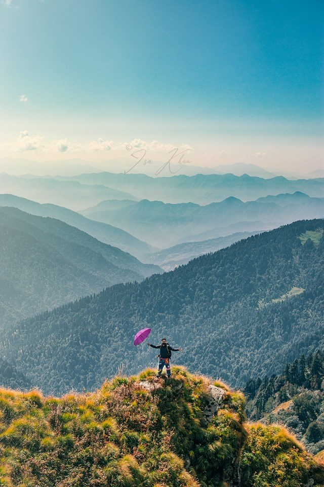 man standing with purple umbrella in front of beautiful mountain valleys in distance india