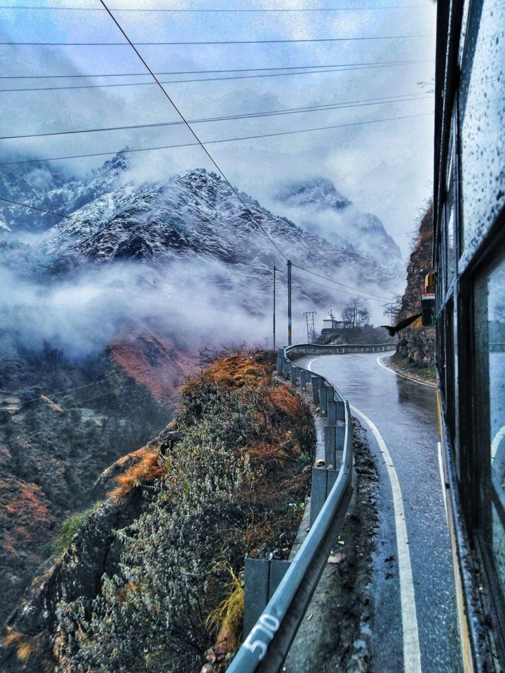photo taken from bus of snowy and cloud covered mountains india