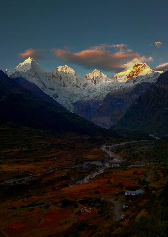 blue and red grass and small village in valley with snowy himalaya mountains in distance india