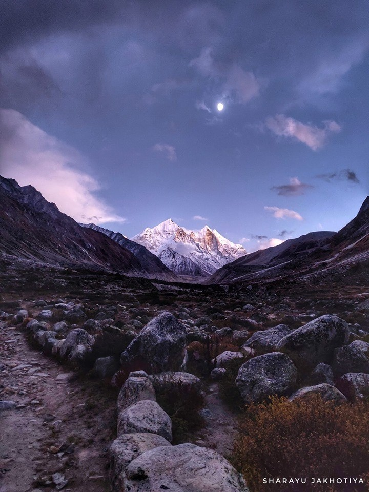 photo of rocks on path with mountain range in distance sunset himalayas india