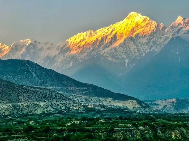 sun shining on top on mountain with green valley in front of it nepal himalayas